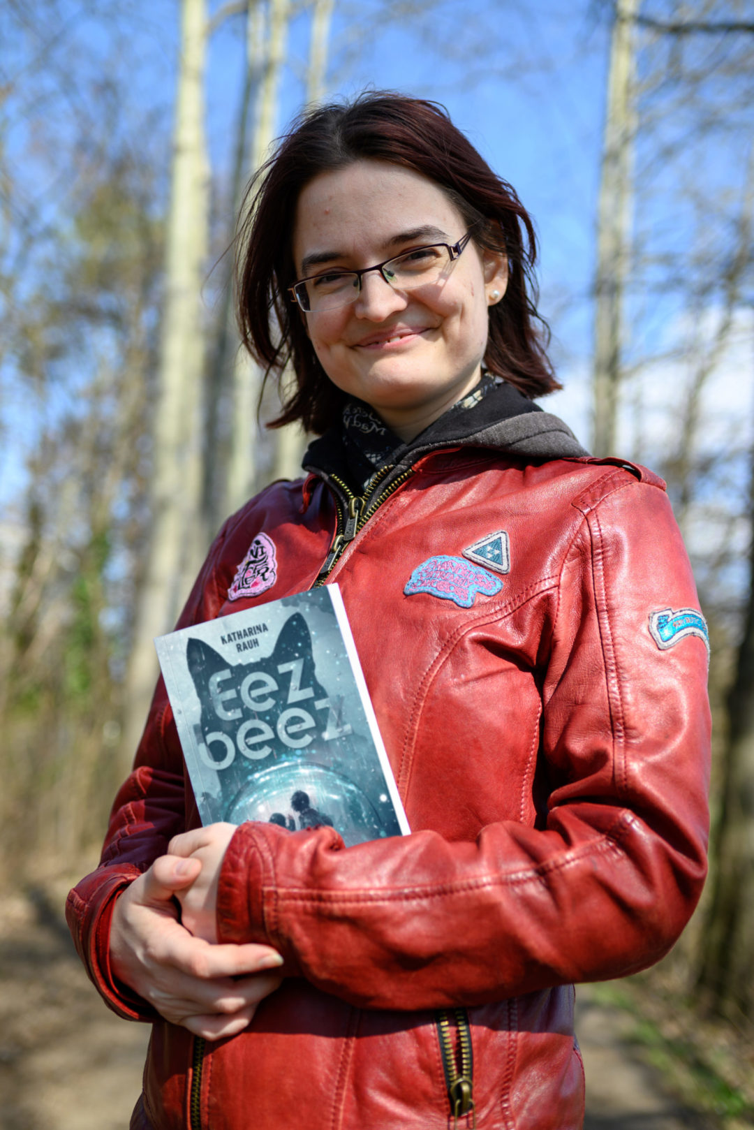 Katharina in roter Jacke mit Buch im Wald
